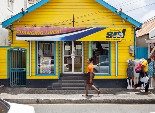Local woman walks by brightly coloured blue and yellow lottery terminal in St. Lucia