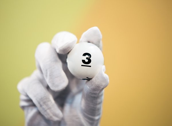 White gloved hand holds up lottery ball showing the number three