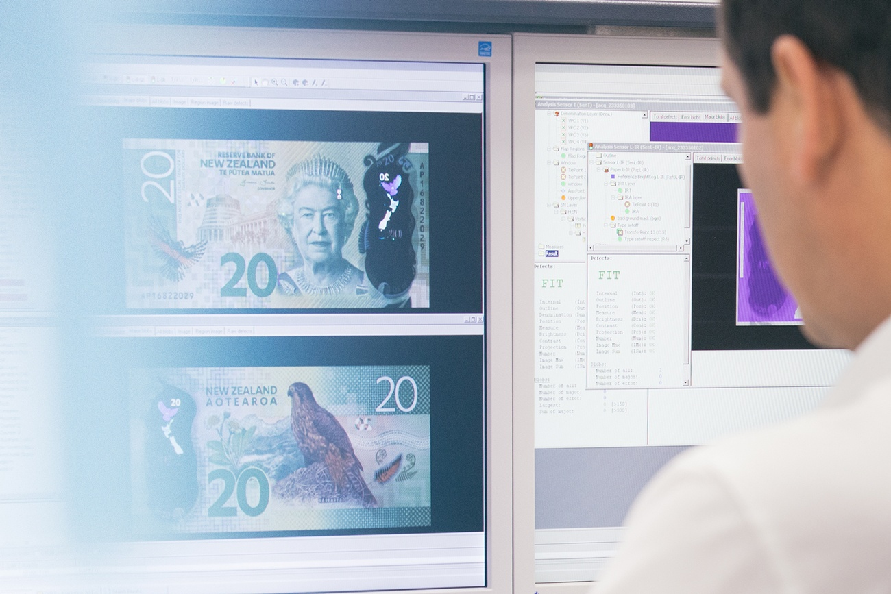 Man looks at computer screen showing 20 New Zealand dollar bill